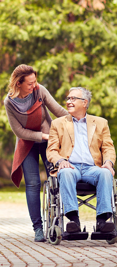 caregiver assisting senior on his wheelchair while smiling