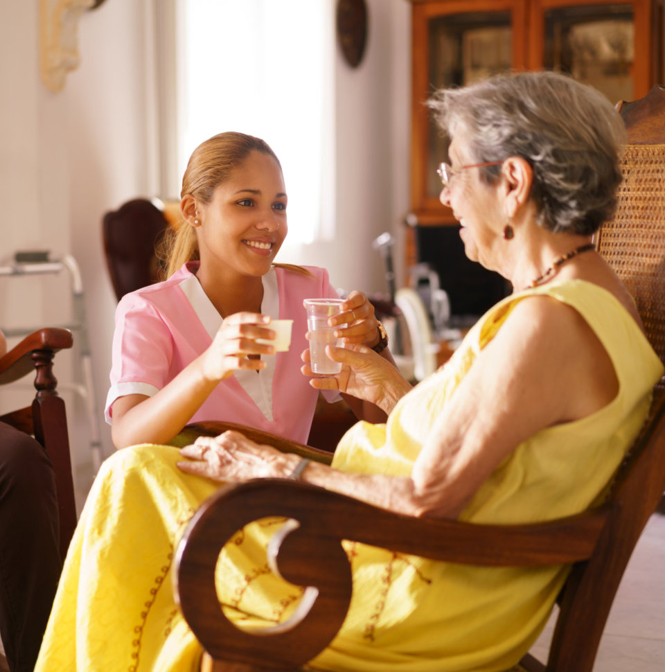 Old people in geriatric hospice: young attractive hispanic woman working as nurse helps a senior woman.