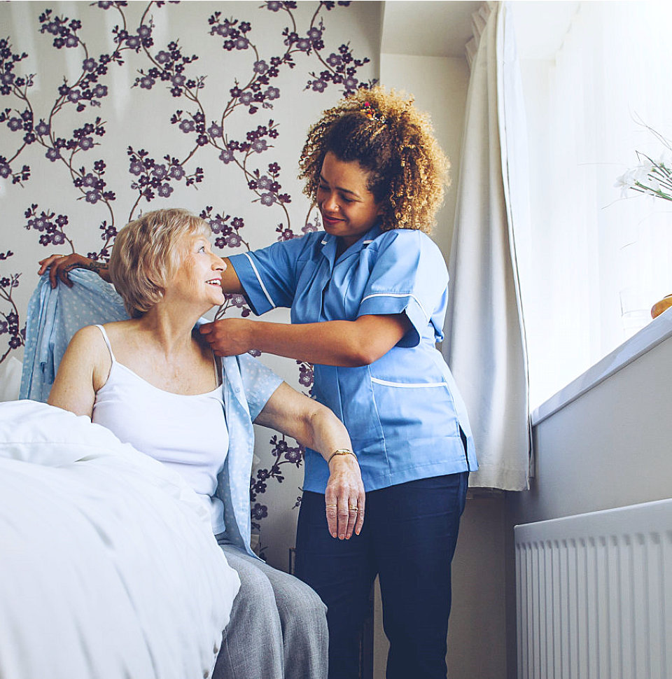 caregiver helping a senior woman on wearing her clothes