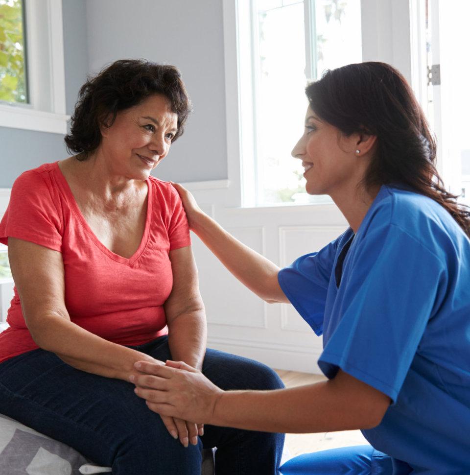 Nurse Making Home Visit To Senior Hispanic Woman