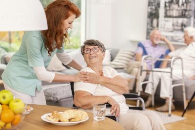 friendly nurse supporting smiling senior woman