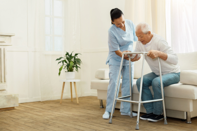 caregiver smiling and helping her patient to stand up